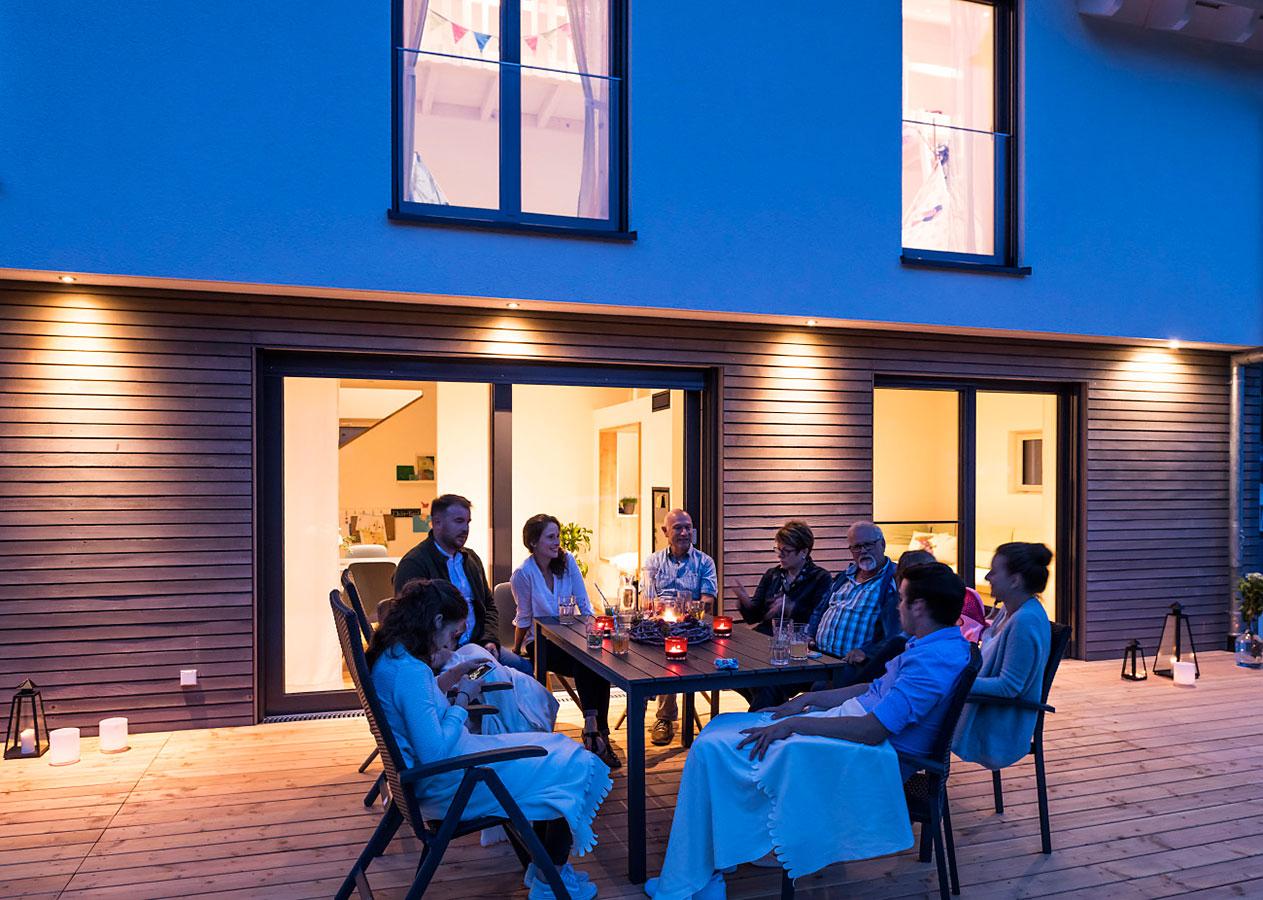 Familie sitzt am Abend auf der Terrasse
